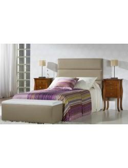 Dormitorio de matrimonio con cabecero tapizado en piel sintética y dos mesillas.